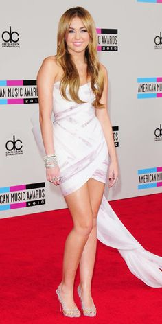 2010 AMERICAN MUSIC AWARDS Cyrus walked the red carpet in a handpainted draped Marchesa cocktail dress and crystal-embellished Christian Louboutin heels.    31      7