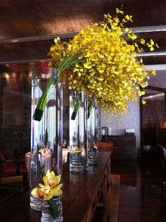 Spray of golden yellow orchids in tall cylindrical vases @Four Seasons Hotel Hong Kong. So dramatic!