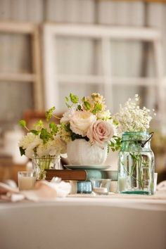 centrepiece - vintage books, mason jars and white vases with assorted flowers and small candles in clear containers