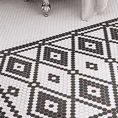A diamond-shaped rug in small black-and-white hex tiles helps define this family bath.