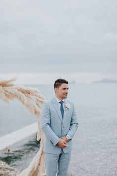 Pale Blue Wedding Suit for Groom at Destination Wedding | By Silvia Sanchez Fotografias | Destination Wedding | Spanish Wedding | Spain Wedding | Intimate Wedding | Pink and Blue Wedding Decor | Pampas Grass Decor | Moon Gate | Neon Sign for Wedding | Groom Wedding Suit | Groom Outfit | Pale Blue Suit Blue Wedding Suit Groom, Wedding Groom, Wedding Suits, Moon Gate, Morning Suits, Grass Decor, Spanish Wedding, Groomsmen Suits, Looking Dapper