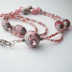 This pink beaded lanyard features a large pink Indonesia bead as the focal point. Other pink beads and decorative silver beads and bead caps are added to the design. Small pink Czech glass crystals ad