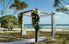 Bamboo wedding arbour with white muslin, floral arrangement and white aisle runner. Gorgeous set up at Villa Champagne, Vanuatu. #Vanuatu #VanuatuWeddings #IslandWeddings #TropicalWeddings #BeachWeddings #PortVila #Evrisamting #Wedding #BambooWedding #BambooArbour #BambooArch