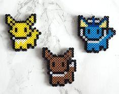 Items similar to Pokemon Eeveelutions Mini Perler Bead Keychain Necklace Earrings Choker- Eevee- Jolteon- Vaporeon- Hypoallergenic- Hama Beads on Etsy Hama Beads Pokemon, 3d Pokemon, Diy Perler Beads, Perler Bead Art, Pokemon Eeveelutions, Pearler Beads, Easy Perler Bead Patterns, Melty Bead Patterns, Perler Bead Templates