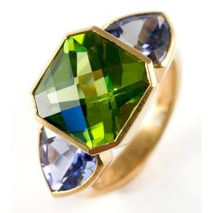 22kt gold, peridot and tanzanite ring. Containing one fancy cut peridot (7.26 cts.) flanked by two triangular tanzanites (4.23 cts.). Designed and made in-house by Julius Cohen New York. Contemporary