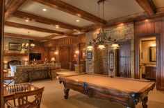 LOVE IT! The lower level open floor plan includes the Recreational room and Billiards room which features stain paneled walls, a coffered ceiling, a stone fireplace flanked with built in cabinets and cue stick holders.