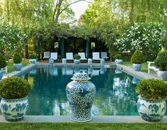 Carolyne Roehm | Plants in overscale porcelain pots ring the pool, which is shaded by a pavilion.
