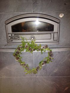 Taivutettu metallihenkari sydämen muotoiseksi, käpyjä, hopeasuihketta ja lopuksi riidenliekoa ympärille.