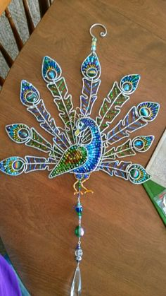 Wire wrapped beaded sun catcher with peacock feathers.                                                                                                                                                                                 More