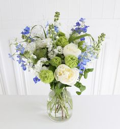This bouquet is the epitome of a fresh summer's day - consisting of bright blue delphinium, light green viburnum opulus, scented white stocks and fluffy white peonies. Brighten someone's day NOW. Artificial Flower Arrangements, Beautiful Flower Arrangements, Floral Arrangements, Beautiful Flowers, Floral Flowers, Blue Flowers, Wedding Bouquets, Wedding Flowers, Online Flower Shop