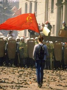 A young man holding a flag of the Soviet Union stands against riot police forces. Russian Figure Skater, Propaganda Art, Black Panther Party, Riot Police, Soviet Art, Military Pictures, War Photography, Power To The People, Communism