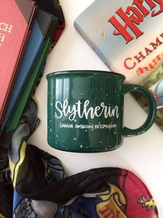 Or perhaps in Slytherin, Youll make your real friends, Those cunning folk use any means, To achieve their ends. The Sorting Hat  Slytherin mugs are here! Hand-lettered, 13 oz green campfire mug. Absolutely lovely and perfect for any Slytherin   Limited quantities right now.  Hand-wash only! ****This mama just had a baby, so therefore theres a 1-2 week shipping window, because who knows when the baby will sleep :) I will ship as soon as Im able. Thanks for understanding