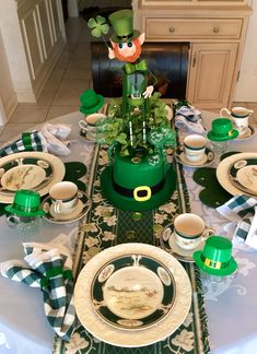 Table set for afternoon St. Patrick's Day afternoon Irish Cream flavored coffee, shamrock shaped petit fours, & scones. Green shamrock cookie cutters serve as napkin rings and guest favors. How I made the leprechaun centerpiece on Irish Eyes r Smiling board.