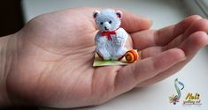 White quilling teddy bear on a hand