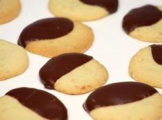 Receita de Cookies de laranja com chocolate - 1 colher (sopa) de raspas de laranja, 1 1/2 xícara (chá) de farinha de trigo, 1/2 xícara (chá) de açúcar, 1/4 xícara (chá) de maisena, 1 pitada de sal, 180 g de manteiga em temperatura ambiente, 1/2 colher (chá) de essência de baunilha, Para o banho de chocolate, 180 g de chocolate meio amargo
