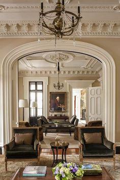 neutral greenroom, classical styling. eyebrow arch doorway, ornate dentil moulding, unique lighting. DesignNashville.com lighting and draperies