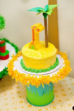 For a simple homemade Safari smash cake, generously frost a 6″ cake with buttercream and use your spatula to form little frosting peaks on the top. Top with a giraffe toy piece + Palm Tree Smash Cake Topper!