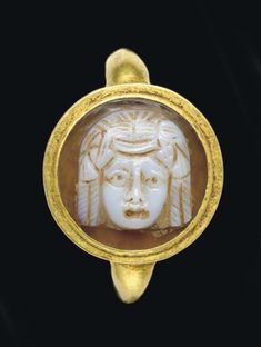 A ROMAN GOLD AND SARDONYX CAMEO FINGER RING   CIRCA 2ND CENTURY A.D.   The plain hoop round in section, joined to a circular bezel set with a cameo in two layers, white on light brown, sculpted with a facing theater mask of a courtesan, her long hair center parted with four thick curls framing her face, her open mouth slightly downturned