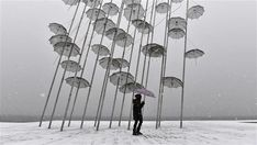 A woman holding an umbrella walks under Greek sculptor artist George Zongolopoulos' 'Umbrellas,' during heavy snowfall in Thessaloniki on January A cold snap gripping Europe has killed more. Thessaloniki, Spiegel Online, Winter Holidays, Les Oeuvres, Wind Chimes, Greek, Culture, Display, Illustration