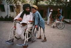 KANDAHAR, AFGHANISTAN. Father and son, both victims of land mines, reading.  Photograph by Steve McCurry.