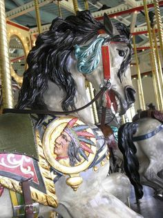 "Cafesjian's Carousel PTC Outside Row Jumper Head Close Up -An oddity of the Cafesjian Carousel is that all horses are what is known as ""dapple gray"" horses. Dapple gray horses are gray with whitish spots scattered over their bodies. Most carousels feature horses with a variety of coat color, particularly white. Many existing carousels have more fanciful color schemes because horses have been repainted over the decades to make them appealing to new generations of young riders."