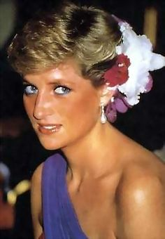 Princess Diana hair upswept with fresh flowers wears a purple off the shoulder gown.