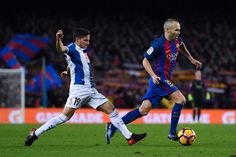 Andres Iniesta of FC Barcelona competes for the ball with Pablo Piatti of RCD Espanyol during the La Liga match between FC Barcelona and RCD Espanyol at the Camp Nou stadium on December 18, 2016 in Barcelona, Catalonia.