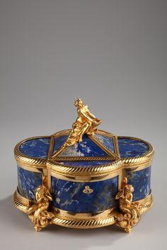 Une superbe boîte à bijoux polylobée en lapis-lazuli et monture en bronze doré, ciselé de côtes torses, sommée d'une pyramide soutenant une nymphe dénudée, les jambes couvertes par...