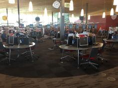 Public PCs in middle of Library. Area demarcated by carpet circle.  Oval tables hold 4 computers each, leaving room on each end for an extra person, stroller, etc. (NW OKC Library)