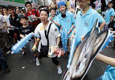A protester hits an image of a wolf representing new Hong Kong Chief Executive Leung Chun-ying