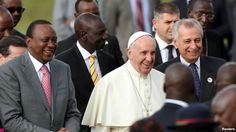 El papa Francisco sonríe mientras camina a la par del presidente keniano, Uhuru Kenyatta (izquierda) a su llegada a Nairobi, Kenia.