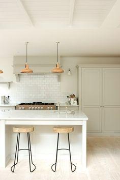 DeVol kitchen with copper pendant lights, marble countertops, Mercury range in truffle and pavillion grey bespoke paint.