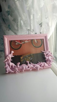 Horizontal light pink picture frame. Features several different dinosaur action figures piled a top one another. Frame measures 8.5 by 6.5, and