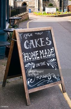 A blackboard sign outside a teashop in the small market town of Aylsham, in Norfolk, eastern England. It states that all their cakes are home-made on the premises. In the background is St Michael's parish church with floral tributes in the graveyard.