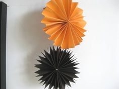 Hanging paper fan Halloween decorations to make with kids to make your house festive for Halloween.