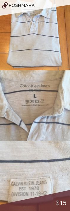 """MENS CALVIN KLEIN LG  POLO SHORT SLEEVE SHIRT This men's shirt is very good used condition. Light grey with white striations and blue stripe. There is extra threading under right armpit see picture 6, this is how the shirt came.   Size Large 22"""" lying flat armpit to armpit  Approx 29"""" shoulder to hem Calvin Klein Jeans Shirts Polos"""
