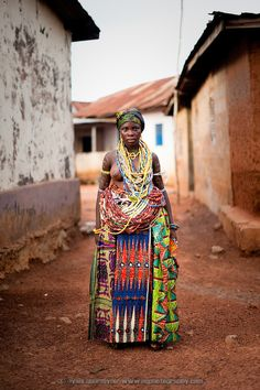 A Dipo-Yo (adolescent girl undergoing Dipo) stands adorned in beautiful beads and cloths on completion of the Dipo puberty rites. T