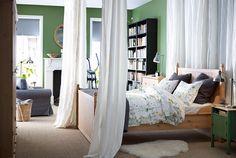 Quarto com cama IKEA, com cortinados atrás e nos cantos inferiores.