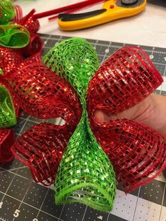A man carefully pinches red mesh—wait until you see his incredible Christmas front door idea!