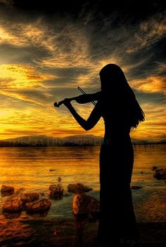 violin in the sunset, across the lake we hear music