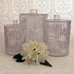 Vintage Mid Century Clear acrylic lucite three piece canister set by Celebrity Inc. New York. The starburst pattern sparkles and refracts color in the light. Excellent unused condition with no signs of wear. Made In USA. This set can hold so many things... bath salts, cotton balls, q-tips, etc.! This shatterproof canister set is perfect for your bathroom or on your vanity. Large Canister is 7 high x 6 wide. Medium Canister is 7 high x 6 wide. Small Canister is 5 high x 4 wide.