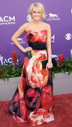 Carrie Underwood  Pretty in a print! The Album of the Year nominee wore a red and black peony print Naeem Khan dress with wide black belt on the red carpet at the MGM Grand Garden Arena in Las Vegas on April 7.