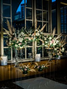 Dramatically lit winter ceremony set up with white and mauve floral with pampas grass, grouped up front and placed on Lucite pillars. Ballroom Wedding Reception, Wedding Reception Flowers, Winter Wedding Flowers, Wedding Ceremony Decorations, Wedding Flower Arrangements, Floral Wedding, Grass Centerpiece, Floral Centerpieces, Winter Wedding Ceremonies