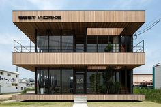 Dubbed Glass + Wood, this combined beauty salon and office building by Hamada Design is clad in strips of red cedar and sits on a high-density industrial site north of Tokyo in Koga, Japan.