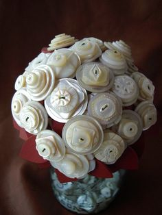 vintage button bouquet. Each bloom is made up of really incredible vintage mother of pearl buttons and has been given a set of red leather leaves.