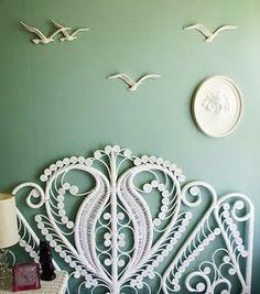 White wicker headboard against a mint green wall. #Bedroom