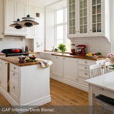 Eine Küche im Landhausstil entsteht durch schöne weiße Küchenfronten und Arbeitsplatten aus Holz. Der Mittelpunkt des offenen Kochbereiches ist eine kleine …