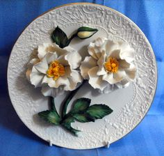 B6897 £DONATED TO CHARITY AUCTION (Jan 2013). A Franklin Mint White Roses of Capodimonte sculptured decorative plate limited edition in heavy hand painted bisque porcelain with border or rim in 22 carat gold.