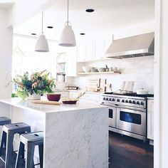 white kitchen + open shelving + waterfall counter