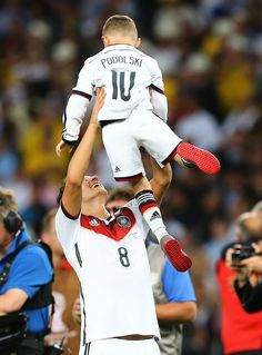 Mesut Oezil of Germany lifts up Lukas Podolski of Germany's son Louis as they celebrate during the 2014 FIFA World Cup Brazil Final match between Germany and Argentina at Maracana on July 13, 2014 in Rio de Janeiro, Brazil.